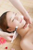 A young woman enjoying spa mask. A young women enjoying facial mask at spa salon, indoors Stock Photography