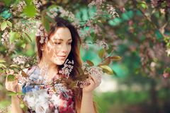 Young woman enjoying spring in the green field with blooming trees stock photography