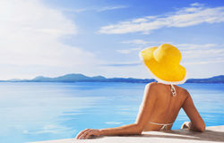 Young woman enjoying summer. Beautiful girl enjoying a sun in the infinity pool. Vacations and summer concept Stock Photo