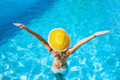 Young woman enjoying summer. Beautiful girl enjoying a sun in the infinity pool. Vacations and summer concept Stock Image