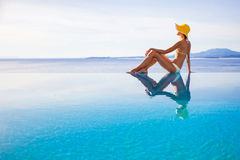 Young woman enjoying summer. Beautiful girl enjoying a sun in the infinity pool. Vacations and summer concept Royalty Free Stock Photo