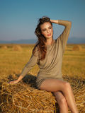 Young woman enjoying summer breeze hay stack Stock Photo
