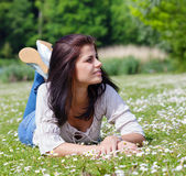 Young woman enjoying summer sunny day in a park. Pretty young woman with dark long hair lying on the grass in a park Stock Photography
