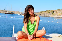 Young woman enjoying the summer vacation sitting on sunbed oon the beach Stock Photos