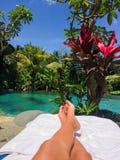 Young woman enjoying the sun bathing. Close to the pool in Ubud, Bali Stock Photography