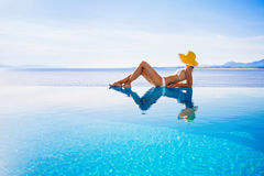 Young woman enjoying a sun. Beautiful girl enjoying a sun in the infinity pool. Vacations and summer concept Stock Photos