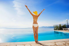 Young woman enjoying a sun. Beautiful girl enjoying a sun in the infinity pool. Vacations and summer concept Royalty Free Stock Photography