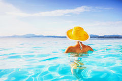 Young woman enjoying a sun. Beautiful girl enjoying a sun in the infinity pool. Vacations and summer concept Stock Photo