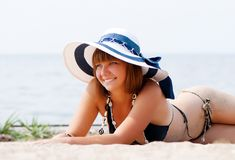 Young woman enjoying the sun laying on a beach Royalty Free Stock Photos
