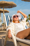 Young woman enjoying sun. On sunbed at tourist resort Royalty Free Stock Images