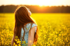Young woman enjoying sunlight in canola field Stock Images