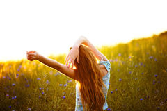 Young woman enjoying sunlight with raised arms in canola field Royalty Free Stock Images