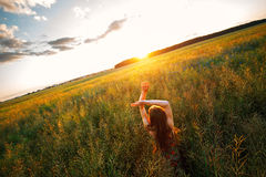 Young woman enjoying sunlight with raised arms in canola field Royalty Free Stock Image