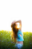 Young woman enjoying sunlight with raised arms in canola field Stock Photography