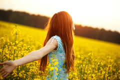 Young woman enjoying sunlight with raised arms in canola field Stock Image