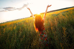 Young woman enjoying sunlight with raised arms in canola field Stock Images