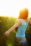 Young woman enjoying sunlight with raised arms in canola field Royalty Free Stock Photography