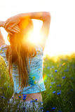 Young woman enjoying sunlight with raised arms in canola field Royalty Free Stock Photo