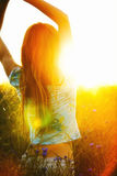 Young woman enjoying sunlight with raised arms in canola field Royalty Free Stock Photos