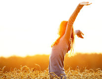 Young woman enjoying sunlight with raised arms in straw field Stock Image
