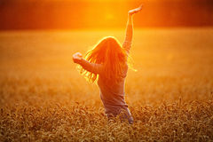 Young woman enjoying sunlight with raised arms in straw field Royalty Free Stock Images