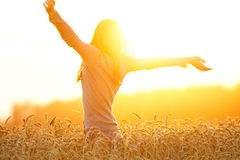 Young woman enjoying sunlight with raised arms in straw field Royalty Free Stock Photos