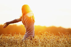 Young woman enjoying sunlight with raised arms in straw field Stock Photo