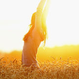 Young woman enjoying sunlight with raised arms in straw field stock images