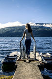 Young woman enjoying the sunny day next to the fjord, Norway. Young woman enjoying the sunny day next to the fjord standing on pier, Norway Stock Image
