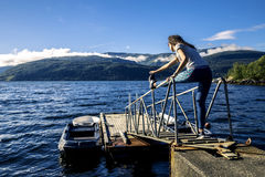 Young woman enjoying the sunny day next to the fjord, Norway. Young woman stretching outside on sunny day next to the fjord, Norway Stock Image