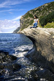 Young woman is enjoying the sunny day on the seaside of Norway Royalty Free Stock Images