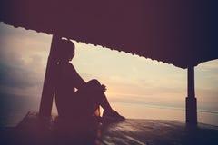 Woman enjoying sunrise near ocean, silhouette. Young woman enjoying sunrise, silhouette. Vintage color Stock Photo