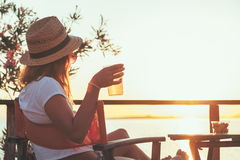 Young woman enjoying sunset at a beach bar. Drinking beer Royalty Free Stock Photography