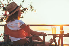 Young woman enjoying sunset at a beach bar. Drinking beer Stock Photo