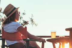 Young woman enjoying sunset at a beach bar. Drinking beer Stock Photography