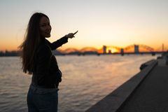 Young woman enjoying a sunset walk along the river Daugava with a view over clear blue sky royalty free stock images