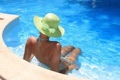Young woman enjoying a swimming pool royalty free stock image