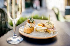 Woman eating spanish pinchos at the bar outdoors. Young woman enjoying tasty appetizer with pinchos, traditional spanish snack, and glass of wine sitting Royalty Free Stock Image