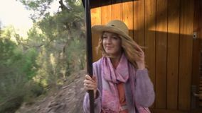 A young woman enjoying traveling on an old train, admiring beautiful tourist locations stock video