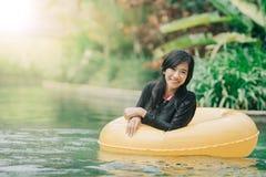 Young woman enjoying tubing at lazy river pool Royalty Free Stock Photos