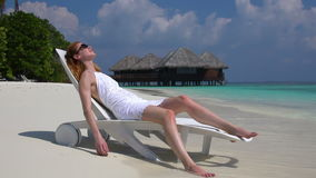Young woman enjoying vacation on a sun lounger on the tropical beach. Slow motion. Young woman enjoying vacation on a sun lounger on a tropical beach. Slow stock video footage