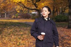 Young woman enjoying walk through park in autumn royalty free stock image