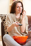Young Woman Enjoying Watching TV Whilst Eating Popcorn Stock Image
