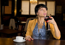 Young woman enjoying wine and coffee. Young woman enjoying a large glass of red wine and cup of espresso coffee while sitting relaxing at a bar counter in a royalty free stock photo