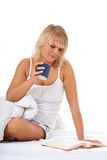 Young woman enjoys cup of coffee in bed Royalty Free Stock Photos