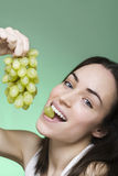 Young woman enjoys eating grapes and turns arround Royalty Free Stock Images