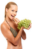 Young woman enjoys eating some grapes. Sexy woman eating grapes isolated on white Royalty Free Stock Photo