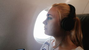 Young woman enjoys the flight, listening to music. Young attractive woman is flying in an airplane. It uses a smartphone listening to music on headphones stock video