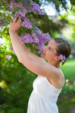 Young woman enjoys blooming lilac Royalty Free Stock Photo