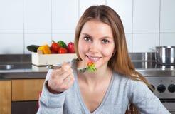 Young woman enjoys fresh salad at kitchen Royalty Free Stock Photos